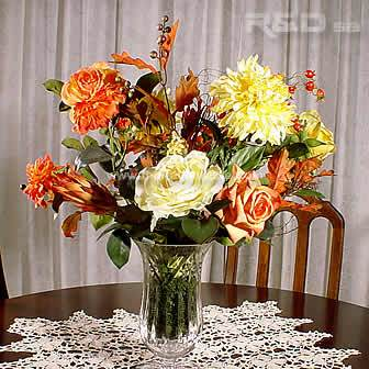 Autumnal silk flowers arranged in a crystal vase
