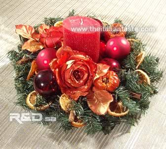Christmas centerpiece with red flowers, fruit and candle