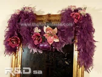 Christmas decoration idea for inside, the photo shows a feather boa decorated with xmas ball and flowers to hang up a door or a wall