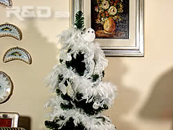 Xmas tree decorated with white feather boa, birds and butterflies