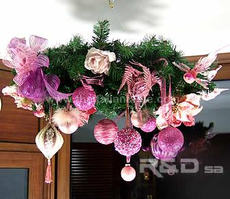 Ceiling wreath for holiday season, decorated with pink balls, butterflies, flowers, birds