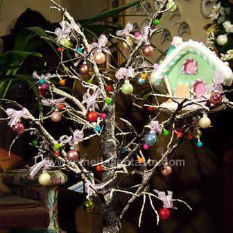 Original little Christmas tree made with snowy leafless branches, decorated with balls and LED lights