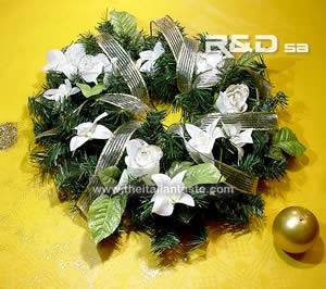 a ring centerpiece with white flowers and pine
