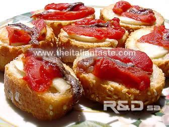Neapolitan little bruschetta, the photo shows bread slices garnished with tomato pieces, anchovy fillets and mozzarella