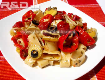 pasta salad with vegetables, the photo shows  a plate full of pasta combined with rings of sweet peppers and slices of zucchini (courgettes) and black olives
