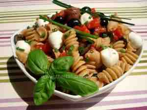 pasta salad, Caprese-style - the image shows short pasta dressed with fresh tomatoes, black olives, mozzarella and basil according to Capri-style