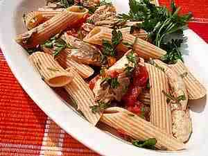 cold pasta with mackerel and tomatoes, the photo shows a detail of pasta dressed with mackerel pieces and tomato pieces