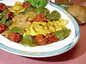 coloured italian ravioli-the photo shows some yellow, red and green ravioli on a dish dressed with tomato sauce and some basil leaves