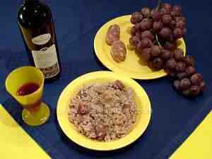 risotto with rosé fresh grapes and sausage accompanied by main ingredients and paired wine