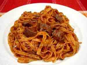 Fettuccine with chicken livers and wild mushrooms served on a white plate