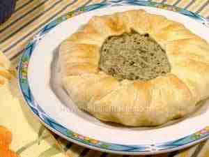 italian savoury pie with ricotta, tuna and courgettes. The image shows the whole pie on a serving plate