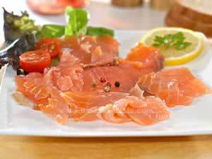 salmon carpaccio, paper-thin salmon slices are arranged on a white serving plate