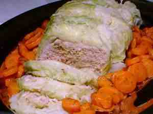 meat roll in savoy cabbage leaves, placed in a serving plate and surrounded by a carrot side dish