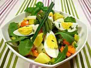 Summer salad with green beans, potatoes, rocket, carrots and eggs
