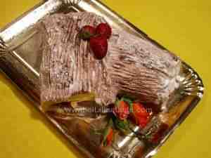 French summer log cake, in the photo you can see the cake decorated with chocolate ice-cream, fresh fruit and roses