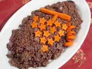 Christmas risotto made with chestnuts, mushrooms and salami and decorated with grape made with carrots