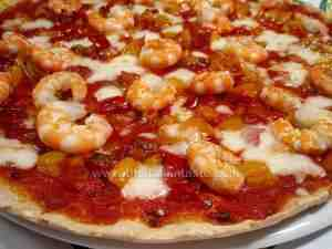homemade italian pizza, on the top there are king prawns and red and yellow bell peppers