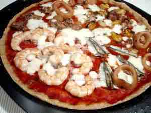 Seafood pizza, the photo shows a detail of the pizza surface with prawns, anchovies, flying squids, mussels and clams