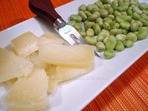 Fava beans (called also broad beans) and pecorino cheese, the photo shows the shelled fava beans, pecorino cut into bite-sized morsels and a glass full of red wine to match this appetizer