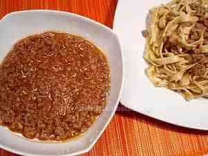 Bolognese tagliatelle, the photo shows a dish with tagliatelle tossed with Italian ragout (meat and tomato sauce) and a bowl with some pasta sauce