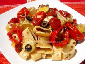 Pasta salad with ring-shaped ingredients, the photo shows calamarata pasta combined with bell pepper rings, black olive slices, courgette (zucchini) slices