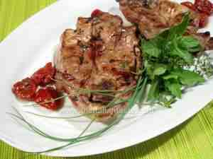 Marinated and grilled lamb, the photo shows two leg steaks, grilled and dressed with olive oil, garnished with aromatic herbs