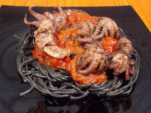 Black spaghetti combined with suid-and-octopus sauce, the photo shows the pasta dish on a black plate