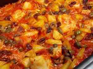 Cod in sauce, Sicilian recipe. The image shows cod pieces in tomato sauce enriched with green olives, capers, pini nuts, sultanas, potatoes