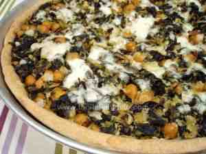Savory tart filled with a mixture of cod, chickpeas, kale and garnished with mozzarella