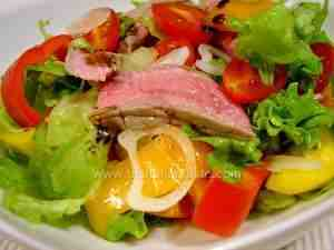 beef salad made with meat, bell peppers, tomatoes, onion and green leaves on a platter