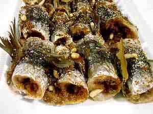 Sardines filled with raisins, pine nuts, bread crumbs, sugar and parsley and then baked