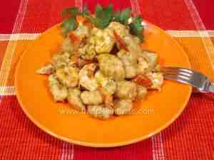 Potato gnocchi dressed with seafood sauce on orange serving platter