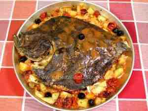 baked turbot in baking pan along with potatoes, olives and tomatoes