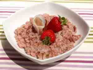 Risotto with strawberries and speck ham on a white bowl