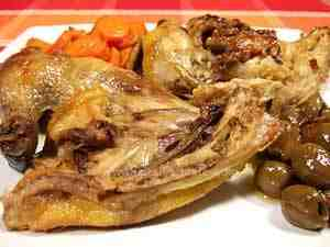 Guinea fowl, cooked in the pot, is served accompanied by olives and carrots